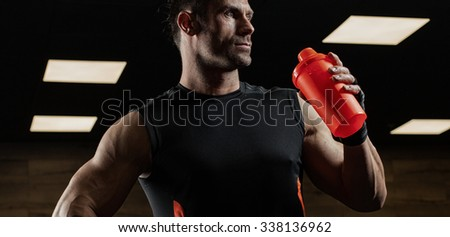 the very muscular sporty guy drinking protein in dark weight room - stock photo