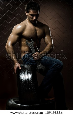 the very muscular workman with rubber-tire and big wrench,  on  netting  steel fence background - stock photo