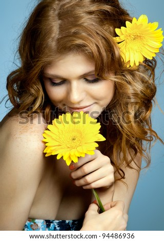 the very  pretty red-haired freckled young woman with yelow flowers on blue background, vertical portrait - stock photo