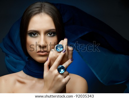 the very  pretty woman with dark blue neckerchief,  rings with huge blue brilliant, sensual sexuality gaze - stock photo
