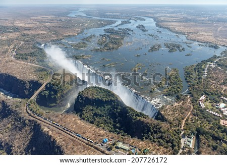 The Victoria falls is the largest curtain of water in the world (1708 m wide). The falls and the surrounding area is the National Parks and World Heritage Site (helicopter view) - Zambia, Zimbabwe - stock photo