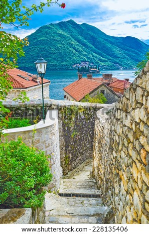 The view from the medieval backstreet on the Kotor bay with the islet of St George, Perast, Montenegro. - stock photo