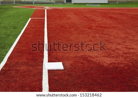 The view is from behind first base looking towards home plate with artificial turf at a school softball field. The bright colors of the artificial turf are a high contrast to a normal playing field. - stock photo