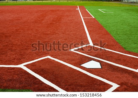 The view is from behind home plate looking towards first base with artificial turf at a school softball field. The bright colors of the artificial turf are a high contrast to a normal playing field. - stock photo