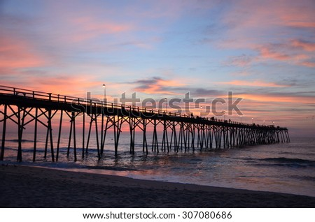 The view near the pier during sunrise at Kure Beach North Carolina on a warm summer morning.