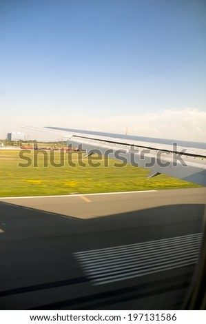 The view of a runway and the grass beside it from an airplane. - stock photo