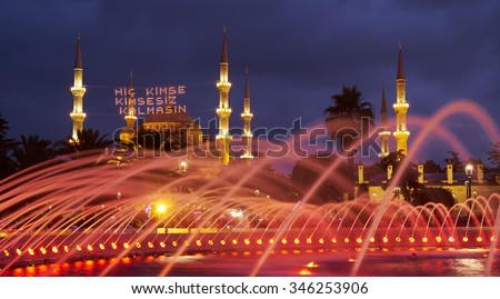 The view of Blue mosque throught the fountain water in the evening illumination. Traditional mahya lights are stretched across the minarets during the holy month of Ramadan, Istanbul, Turkey - stock photo