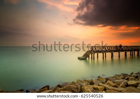 The view of burning sunset with old jetty at beach. Sungai Lurus Batu Pahat Johor. This image may contain noise ,blurry clouds due to long exposure, soft focus and poor lighting