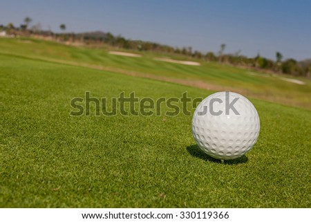 The view of macro golf ball and the green golf course background. - stock photo