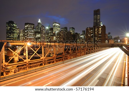 The view of the Financial District in New York City behind traffic on the Brooklyn Bridge. - stock photo