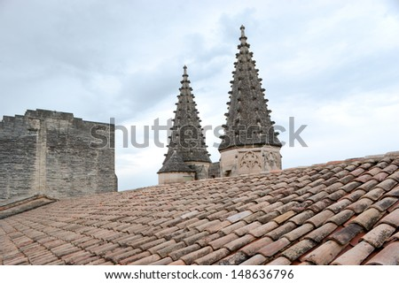 The view on the stone spires located on the facade of Papal Palace of Avignon. - stock photo