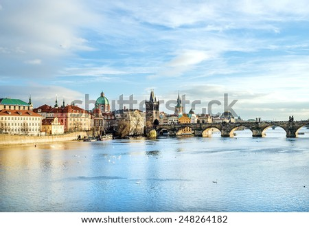 The view over the Vltava river, Charles bridge and white swans from Mala Strana in Prague, Czech Republic, on a clear sunny winter day - stock photo
