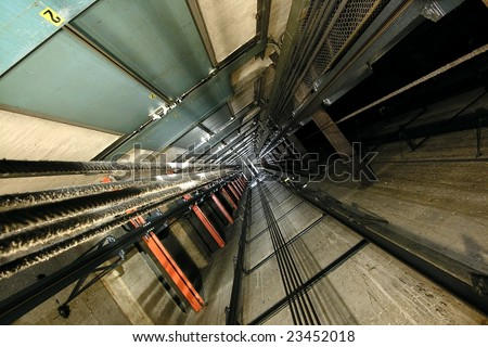 The view up inside a tall elevator shaft. - stock photo