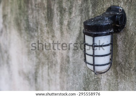 The vintage lamp on gray cement wall background - stock photo