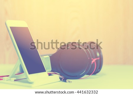 The vintage of smartphone and headphones,smartphone and earphone close up ,music concept - stock photo