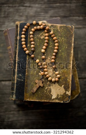 the vintage rosary beads on old book - stock photo