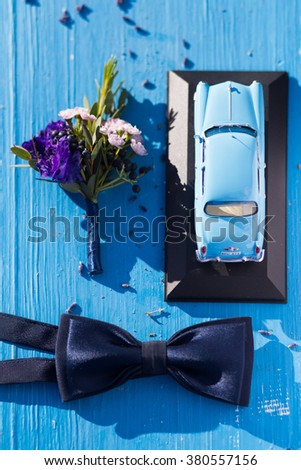 The violet and white groom's boutonniere is lying on the blue wooden background with a small car model and dark-blue wedding bow tie - stock photo