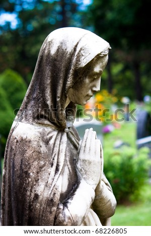 The Virgin Mary Statue praying in a garden - stock photo