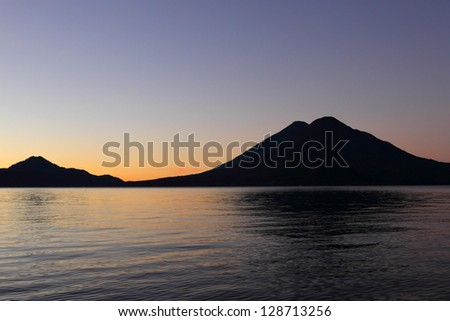 The volcanoes of Lake Atitlan shilouetted against the evening sky. - stock photo