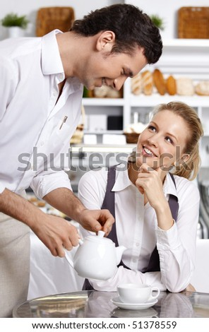 The waiter pours tea to the attractive girl - stock photo