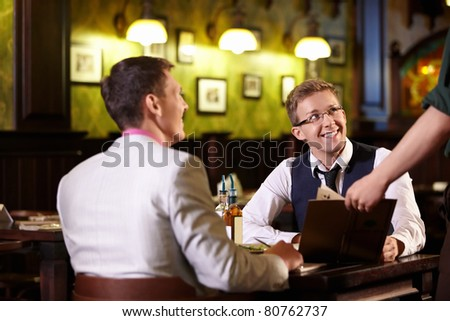 The waiter shows men in a pub menu - stock photo