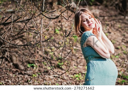 The wakening of spring. Beautiful fair hair woman with tender face and near the tree with turgid buds - stock photo