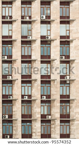 The wall of office building with windows and air conditioners - stock photo