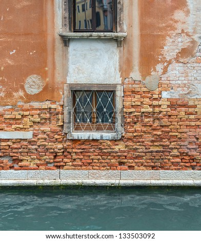 The wall with windows of the medieval house on the canal - Venice, Italy