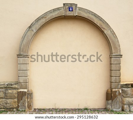 The walled up door with stone arch with metal rusty blue table with white number four on the ancient beige plastered walls background, photo frame, text place  - stock photo