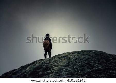 The wanderer on the summit. Hipster, dark colors