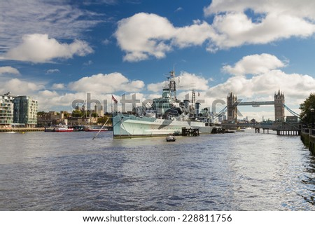 The warship on the river Thames on a cloudy autumn day, with the Tower of London and Tower Bridge in the background. - stock photo