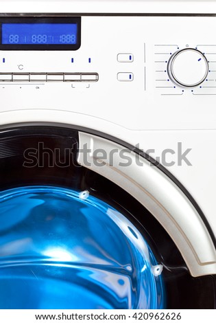 The washing machine - a close up of the display, the manhole and a choice of programs