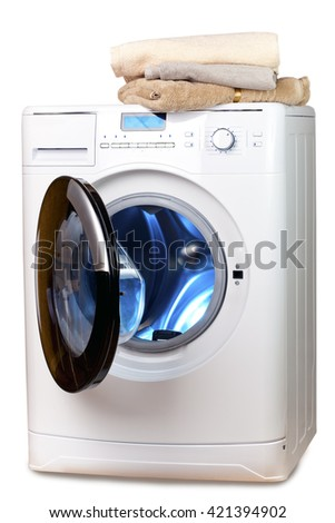 The washing machine with an open door and linen - stock photo