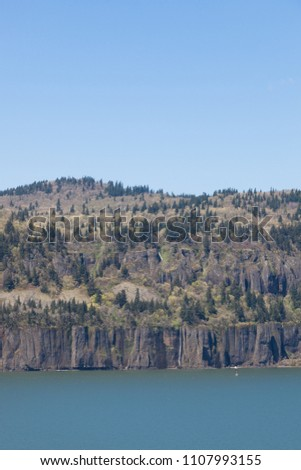 The Washington embankment of the Columbia River Gorge with tall snow melt waterfalls flowing down the rocks to the Columbia River.