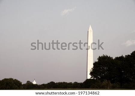 The Washington Monument from a distance with the sky and clouds in the background.