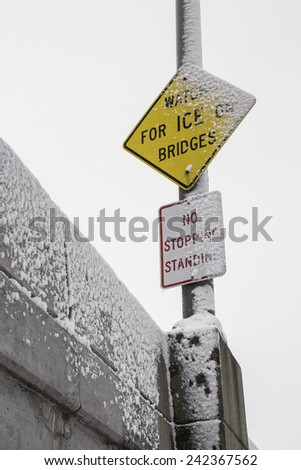"""The """"Watch for Ice on Bridges"""" sign in the snow.  - stock photo"""