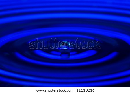 The water drop falls in dark blue water with dispersing circles close up - stock photo