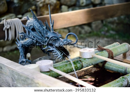 The water is coming out from a stone dragon.Locals take the water to wash hands before go into the temple. - stock photo