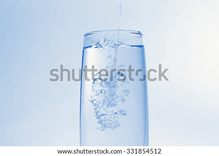 the water pouring in transparent glass with bubbles of air