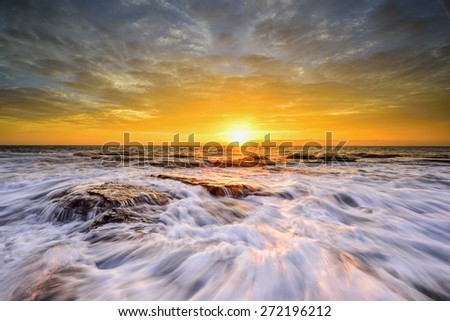 The wave flows over weathered rocks and boulders at North Narrabeen rockshelf in sunrise. Sydney Australia - stock photo