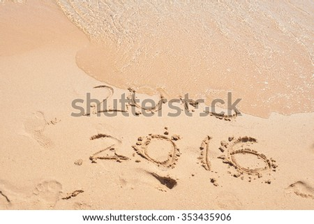 The wave is covering the digits 2015. New Year concept. Inscription 2015 and 2016 on a beach sand. Happy New Year 2016. - stock photo