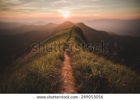 The way of climax. Mountain slope have a way for walk. Background is sunset. - stock photo