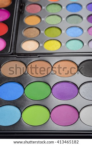 The wealth of palettes in the foreground of the camera. Rich colorful gamma of different tints and hues for perfect make-up. - stock photo