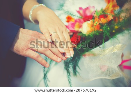the wedding, the bride and groom hand in engagement rings - stock photo