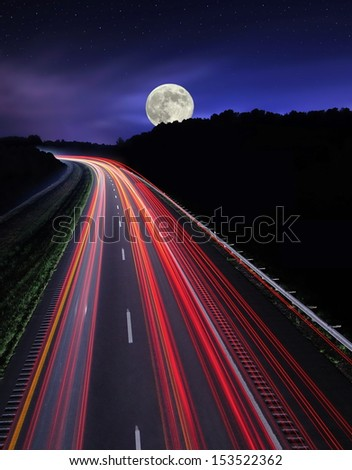 The westbound lanes of Ohio Interstate 70 under a starry, moonlit sky. This image was shot with a slow shutter speed making the traffic appear as streaks of light. - stock photo