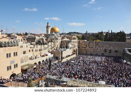 The Western Wall in Jerusalem temple. The area in front of it filled with people from morning prayers. The most joyous holiday of the Jewish people - Sukkot. - stock photo