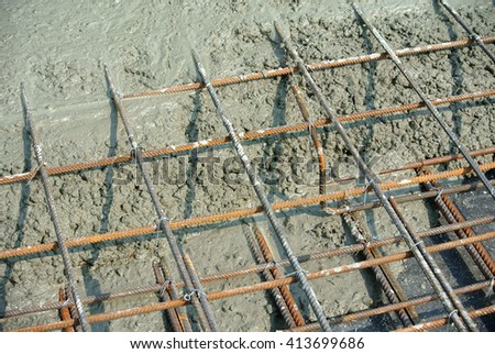 The wet concrete is poured on a steel reinforcement to form strong floor slabs. - stock photo