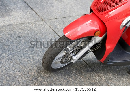 The wheel of a red moped on marble looking tiles. - stock photo