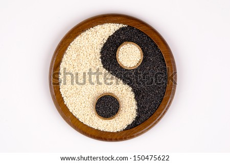 The white and black sesame seeds is yin yang on a white background (Sesamum orientale L.). - stock photo