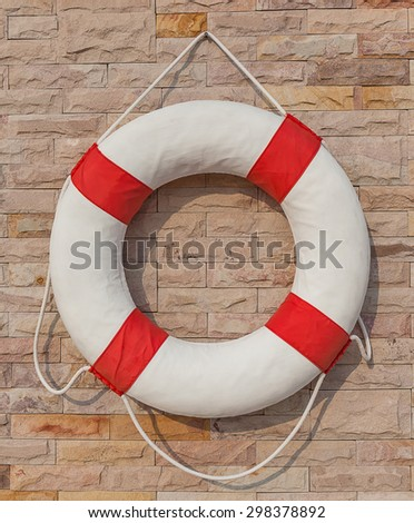 The white and red life buoy hanging on the brick wall around the swimming pool, for safety and rescue. - stock photo